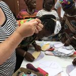 Women standing up as they learn to sew in Sierra Leone