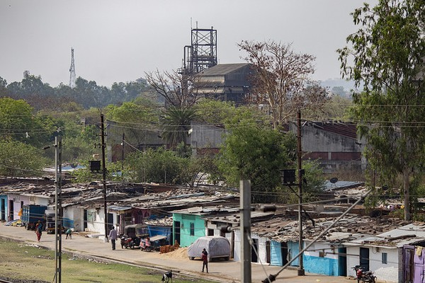 Photo of the shanty-town of Bhopal with the Union Carbide pesticide plant still towering in the background