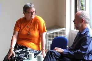 two people discussing a 'what can we do' meeting, over a cup of tea